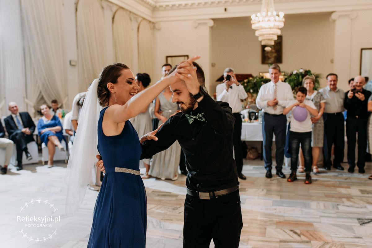 Kobieta w niebieskiej sukni tańczy z panem w czarnej koszuli