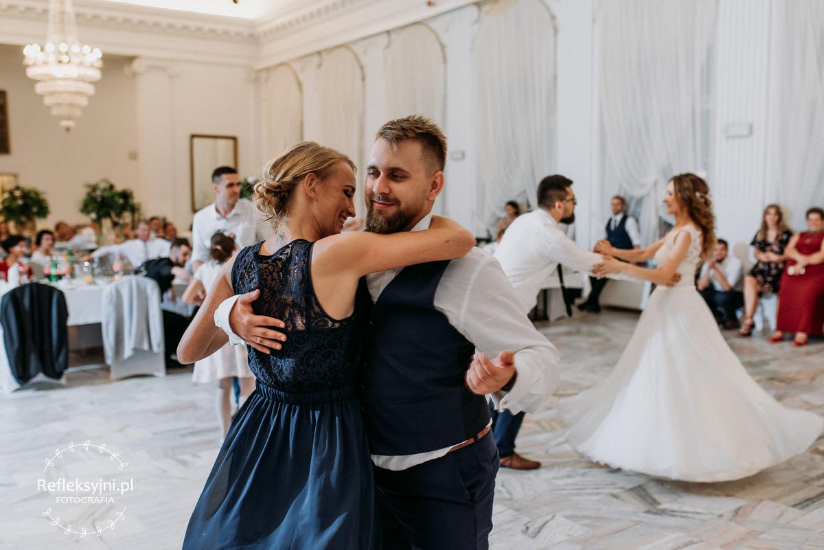 Pan Młody tańczy z kobietą w niebieskiej sukni