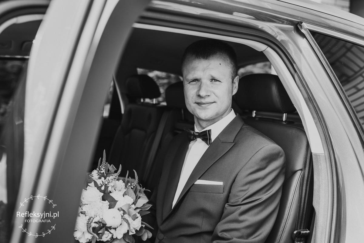 Pan Młody siedzący w samochodzie ślubnym