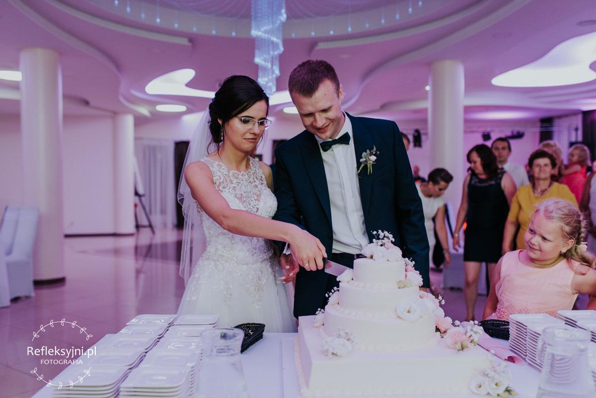 Państwo Młodzi jedzący tort weselny