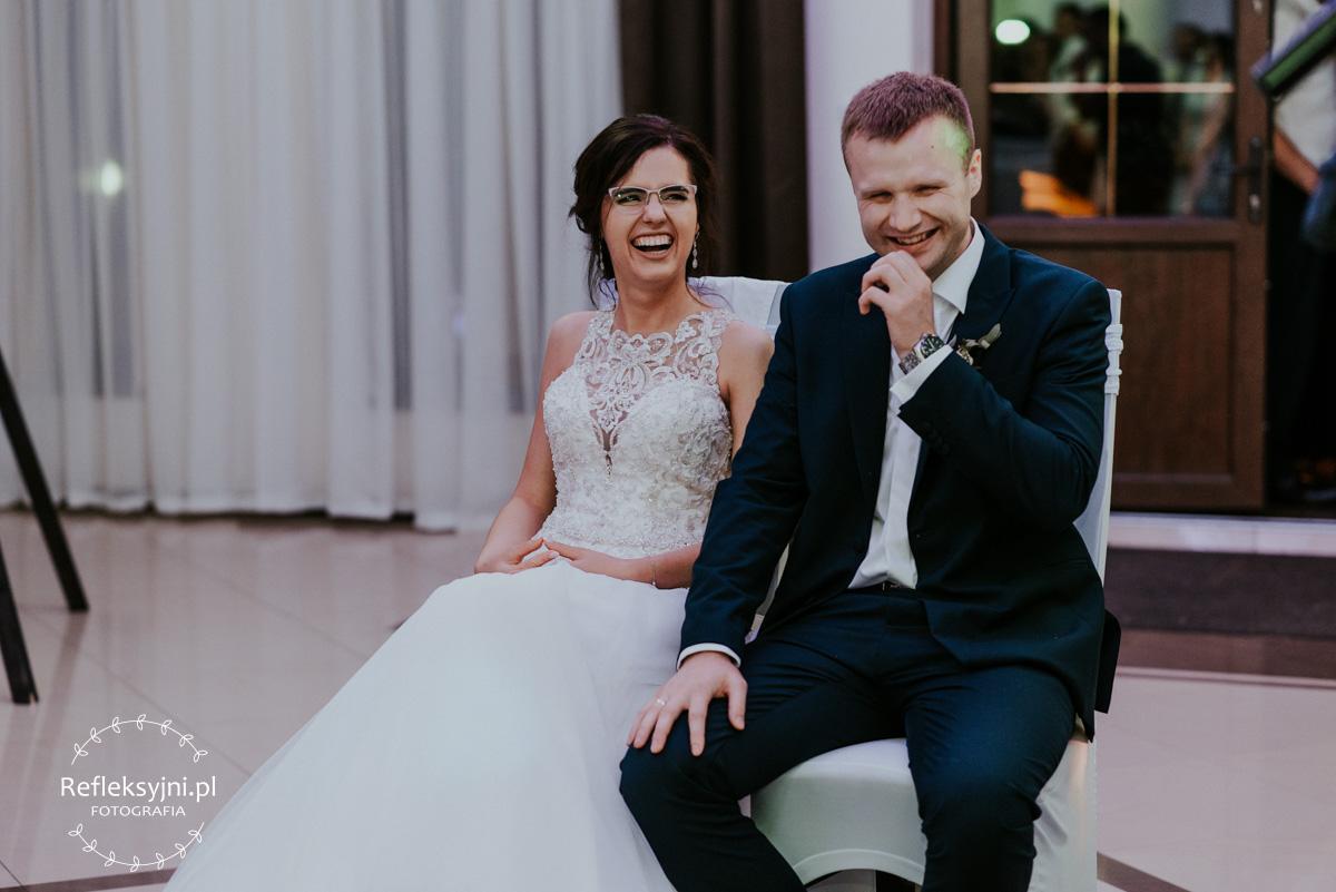 Państwo Młodzi śmiejący się podczas oczepin ślubnych