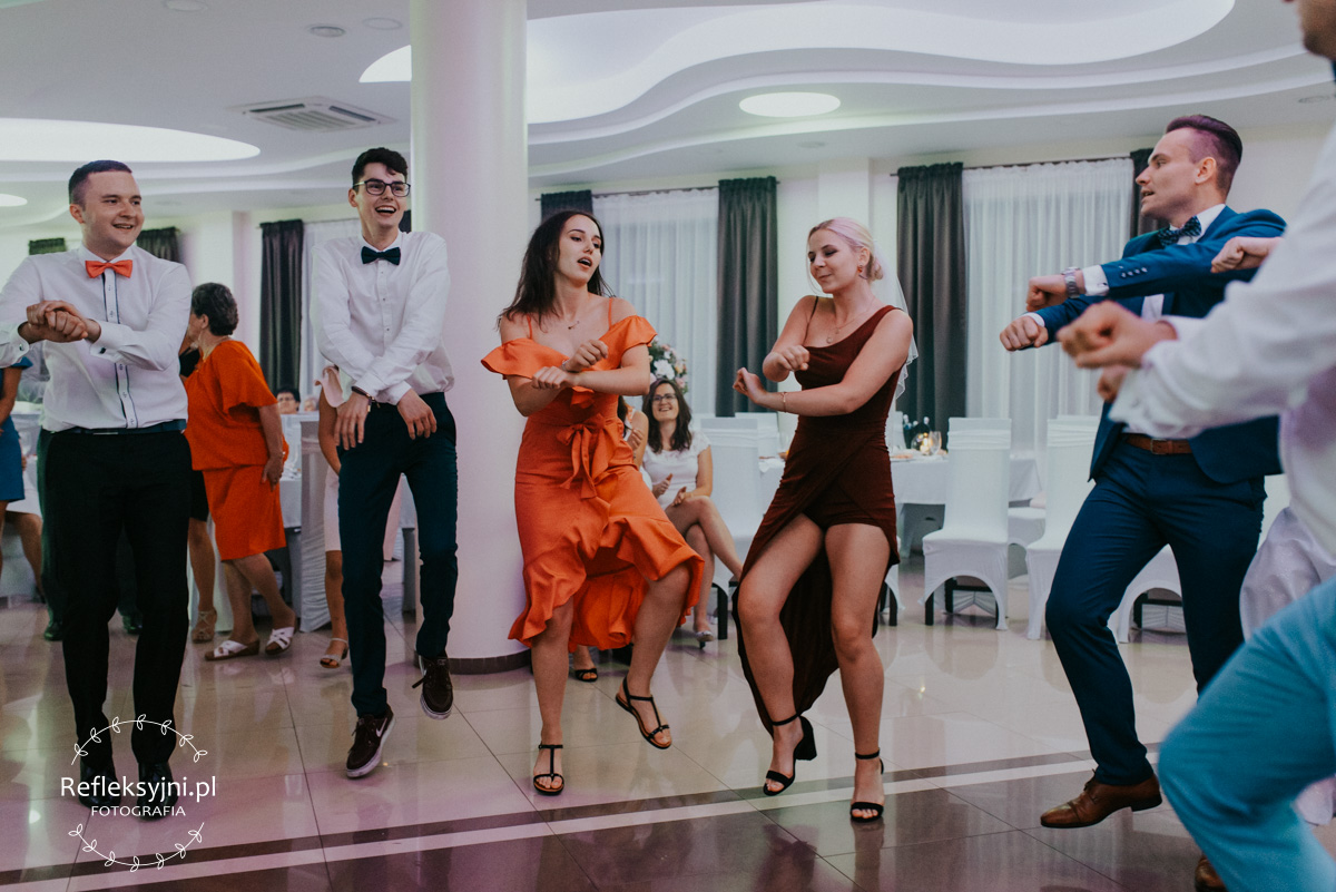 Zdjęcie przestawia gości na weselu bawiących się podczas oczepin ślubnych