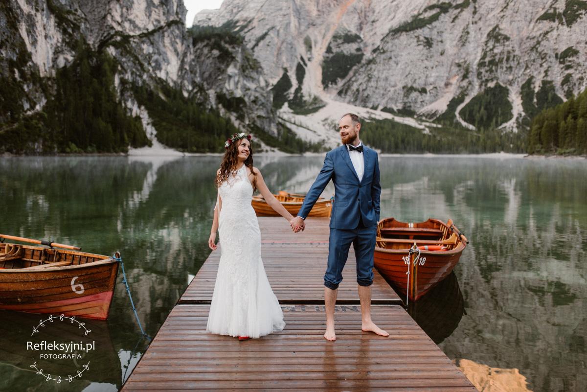 Obraz przedstawia Parę Młodą na drewnianym pomoście w Lago Di Braies w Dolomitach