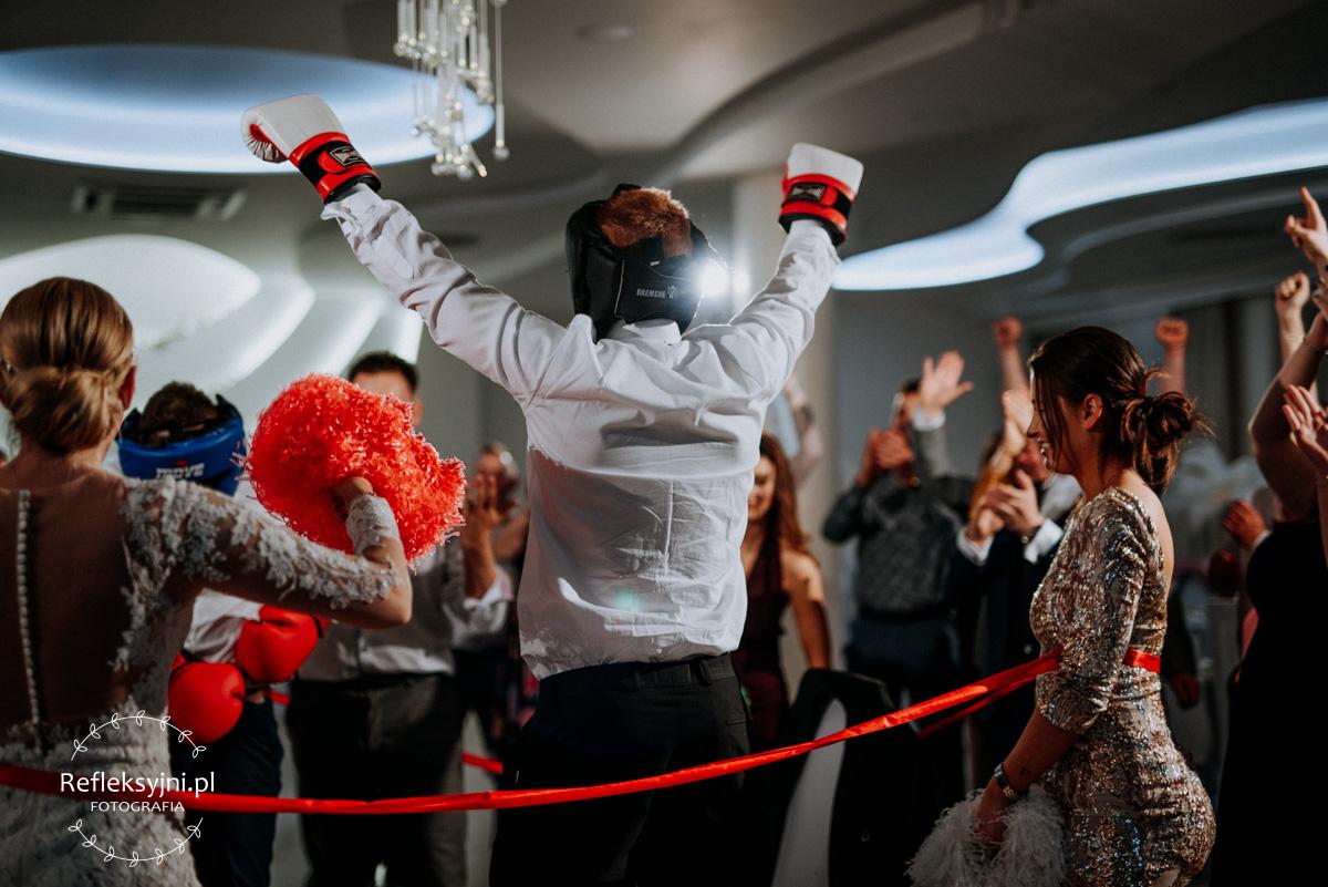 Gość weselny w kasku i rękawicach bokserskich podczas oczepin