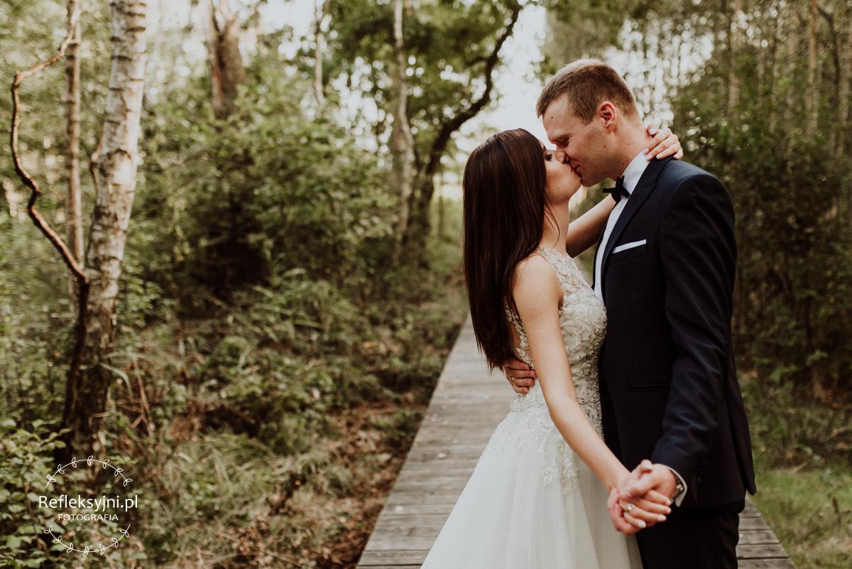 Państwo Młodzi w namiętnym pocałunku na drewnianej kładce
