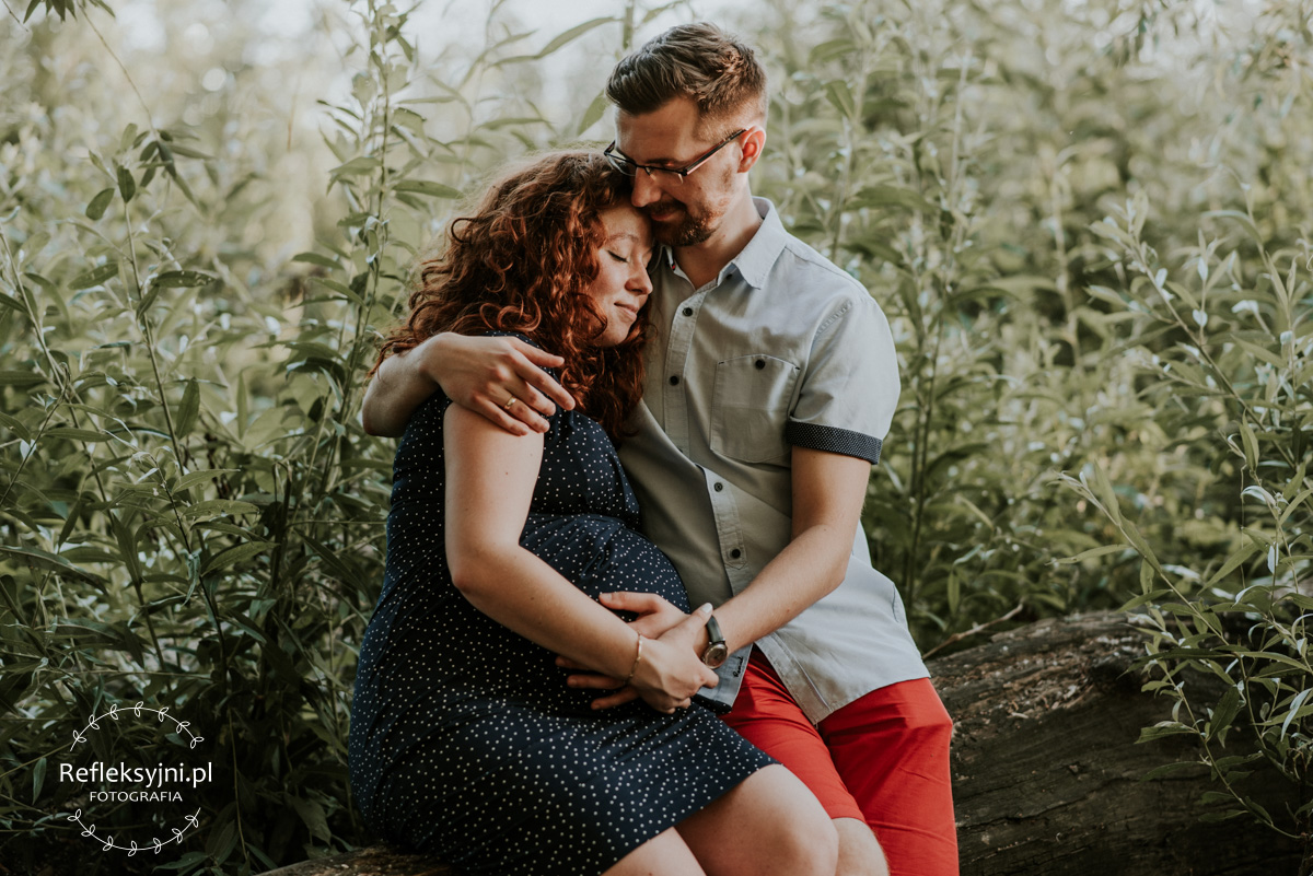 Sesja ciążowa Ruda kobieta i mężczyzna siedzą w lesie
