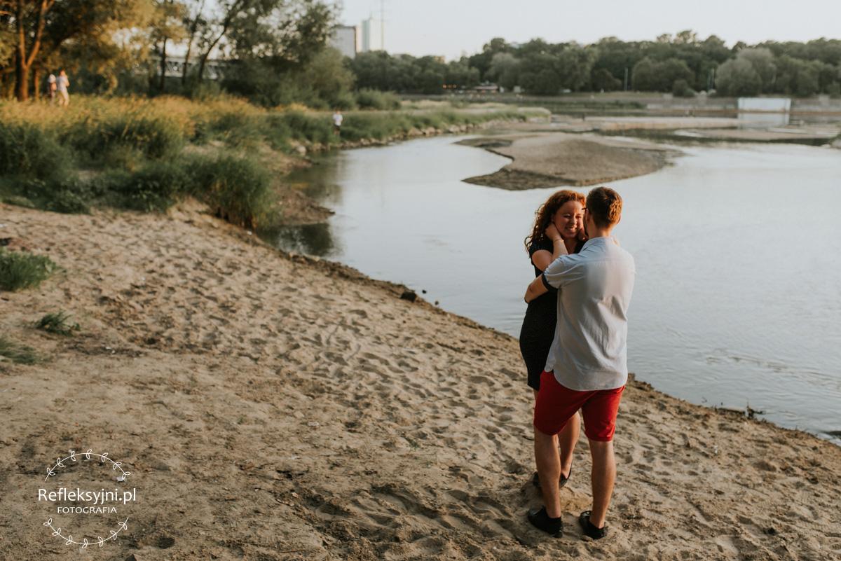 Ruda kobieta w ciąży i mężczyzna stojący na plaży nad Wisłą