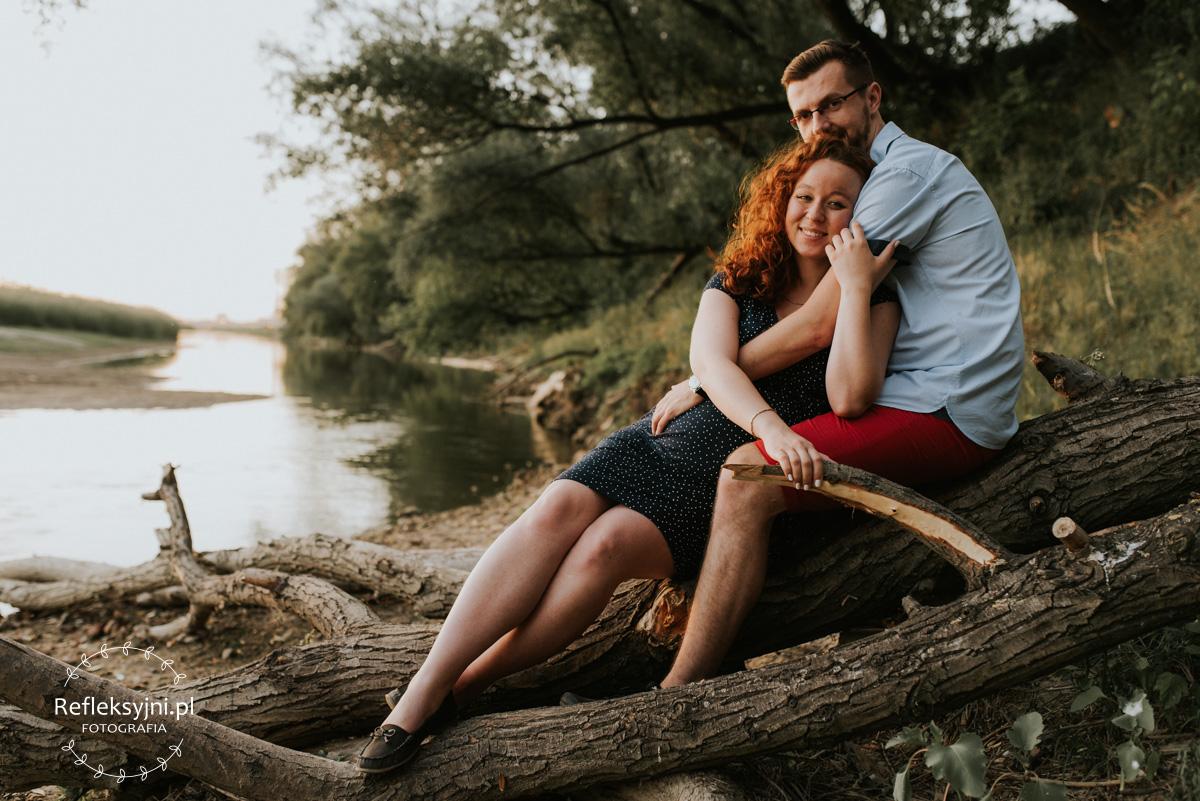 Ruda kobieta w ciąży i mężczyzna siedzący na pniu nad Wisłą