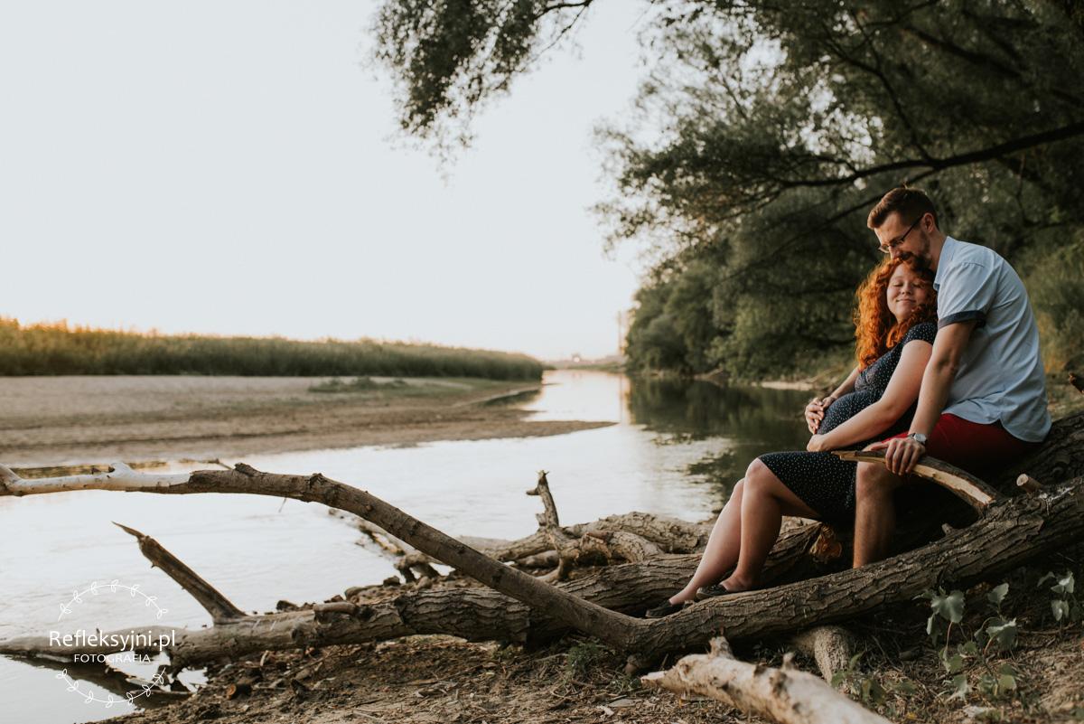 Kobieta i mężczyzna siedzący na pniu nad Wisłą