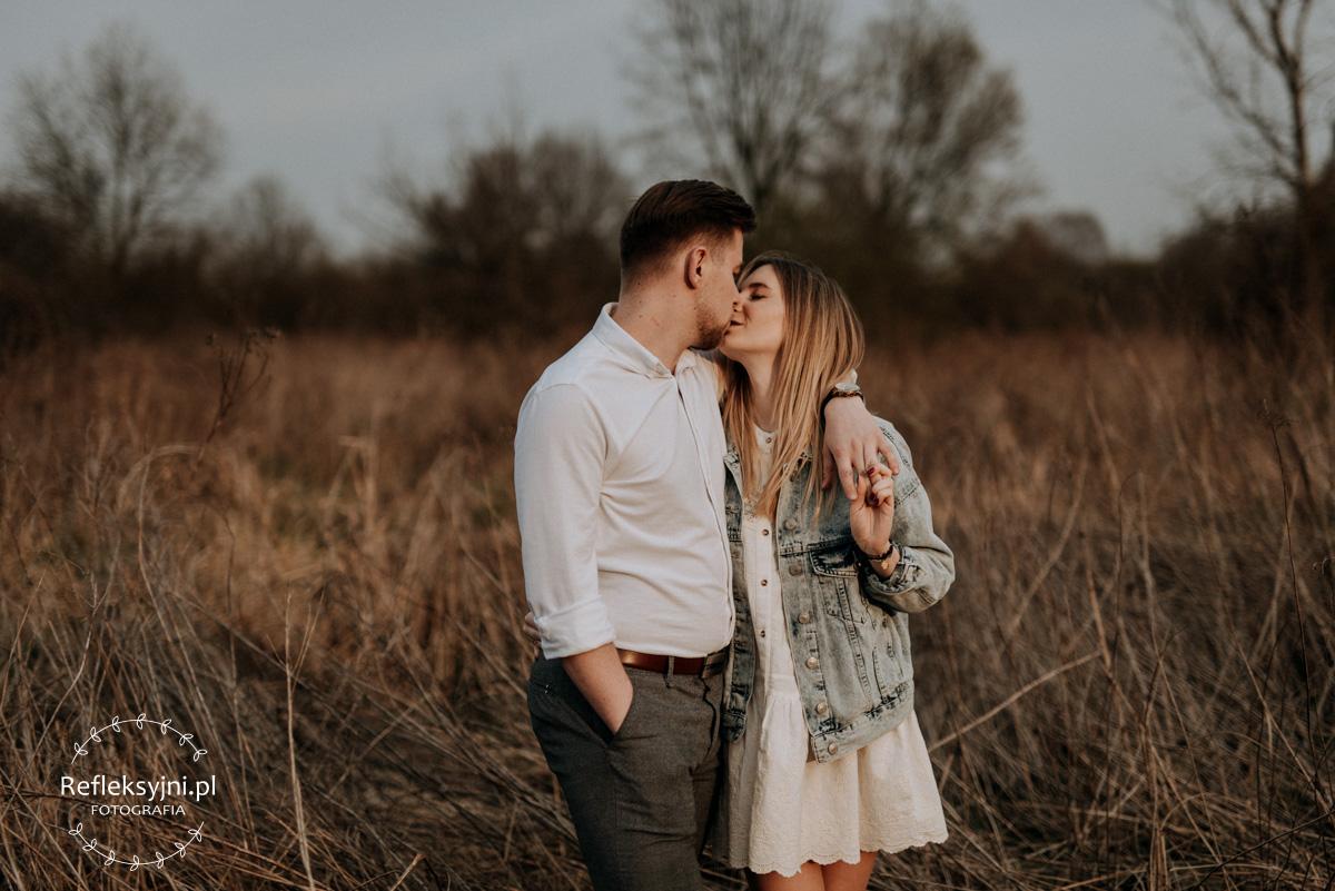 Mężczyzna i kobieta całujący się na polanie