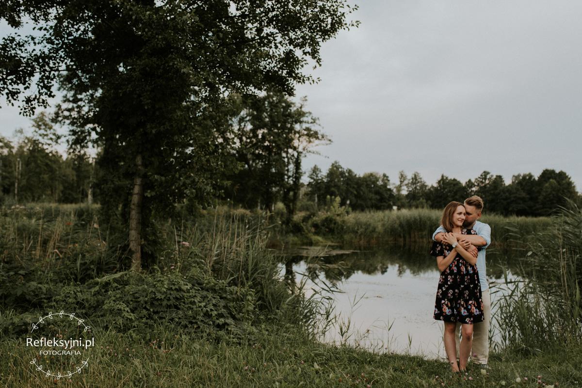 Para narzeczonych podczas sesji narzeczeńskiej na tle jeziorka