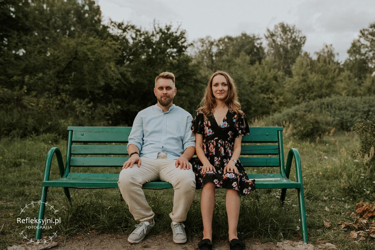 Para narzeczonych podczas sesji narzeczeńskiej siedzący na ławce